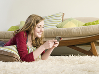 Caucasian woman using cell phone on carpet