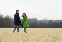 Caucasian couple walking in rural field