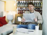 Caucasian man reading newspaper in armchair