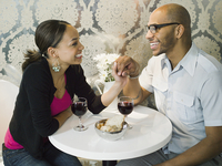 African American couple holding hands at restaurant