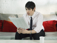 Asian businessman reading newspaper on sofa