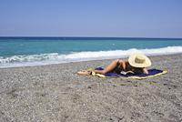 Woman sunbathing and reading on beach