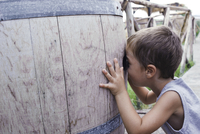 Caucasian boy peering into barrel