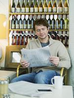 Caucasian man reading newspaper in restaurant