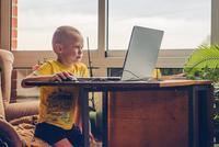 Caucasian boy using laptop at desk
