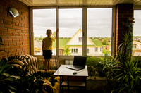 Caucasian boy looking out living room window