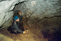 Caucasian climber exploring rock cave