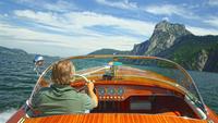 Caucasian man driving speedboat on remote lake