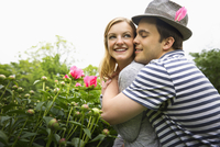 Caucasian man hugging girlfriend in garden