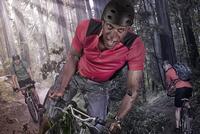 Caucasian man riding mountain bike in forest