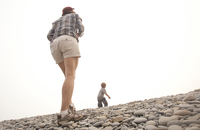 Caucasian mother and son walking on rocky hillside