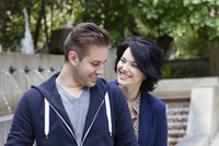 Caucasian couple smiling by urban fountain