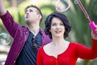 Caucasian couple blowing bubbles outdoors
