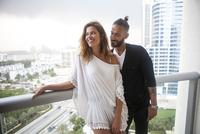 Hispanic couple standing on urban balcony
