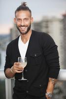 Hispanic man drinking wine on urban balcony