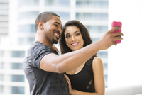 Couple taking selfie with cell phone on urban balcony