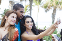 Friends taking selfie with cell phone outdoors