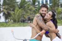 Hispanic couple hugging on bicycle on urban beach