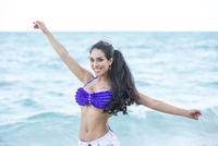 Hispanic woman playing in ocean