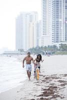 Couple riding bicycle on urban beach