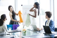 Business people examining fabric samples in office meeting