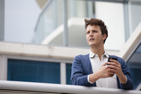 Caucasian businessman using cell phone on balcony