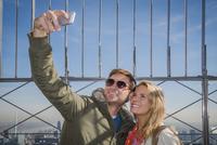 Caucasian couple taking selfie over New York cityscape, New York, United States