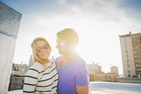 Caucasian couple hugging on urban rooftop