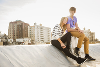 Caucasian couple sitting on urban rooftop