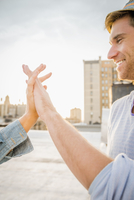 Caucasian couple holding hands on urban rooftop
