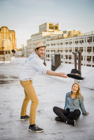 Caucasian couple playing on urban rooftop
