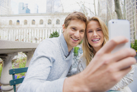 Caucasian couple taking selfie with cell phone in city