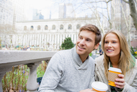 Caucasian couple drinking coffee in city