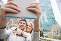 Caucasian couple taking selfie with digital tablet in city
