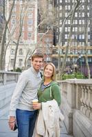 Caucasian couple smiling on city sidewalk