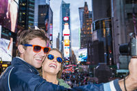 Caucasian couple taking selfie in Times Square, New York City, New York, United States