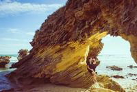 Caucasian man drinking water bottle under rock formation on beach