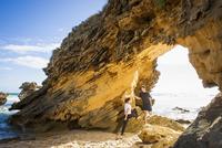 Caucasian couple talking under rock formation on beach