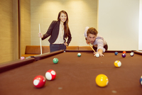 Business people playing pool in games room