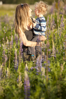 Caucasian mother hugging son in tall grass