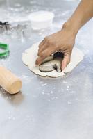 Baker using cookie cutter in dough