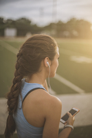 Mixed race athlete listening to mp3 player on sports field