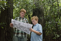 Caucasian boys reading map in forest