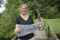 Caucasian woman reading map on footbridge in forest