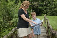 Caucasian mother and son reading map on footbridge in forest