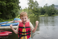 Caucasian boy wearing lifejacket by lake