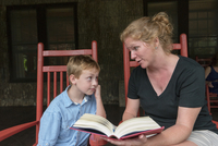 Caucasian mother and son reading on patio