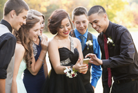 Teenagers using cell phone before prom