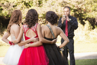 Teenagers taking pictures with cell phone before prom