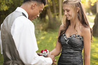Teenage boy attaching corsage to prom date